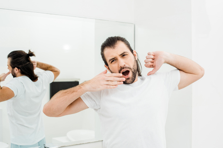 Man in T-shirt stretching and yawning in white bathroom