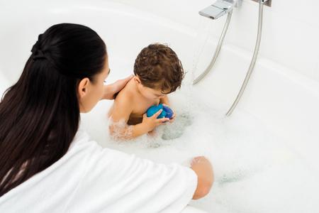 Woman washing toddler boy in white marble bathroom Standard-Bild - 112228576
