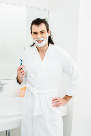 Handsome man shaving and smiling in bathroom 스톡 콘텐츠