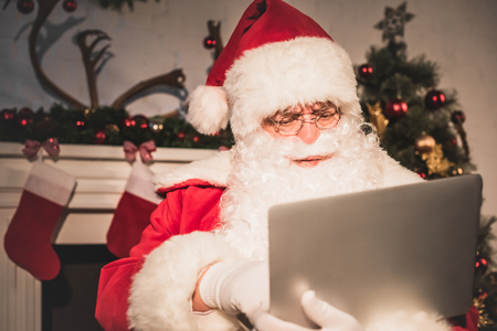 serious santa claus using laptop near fireplace