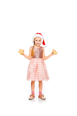 smiling little child in santa hat with ginger cookies looking at camera isolated on white