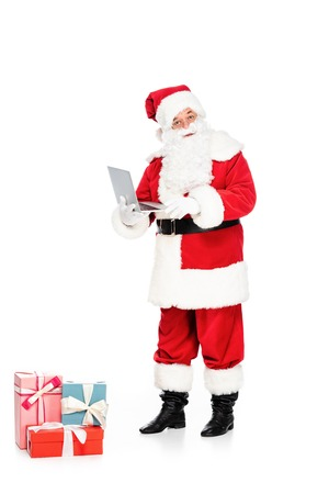 santa claus with presents holding laptop and looking at camera isolated on white