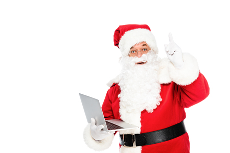 santa claus holding laptop and looking at camera while pointing up isolated on white