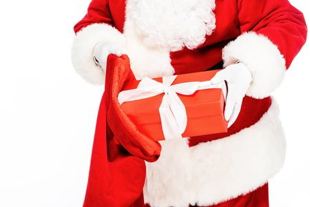 cropped shot of santa claus putting present into bag isolated on white Stock Photo