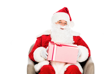 santa claus sitting in armchair with gift box and looking at camera isolated on white Stock Photo