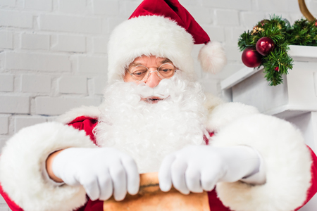 santa claus holding parchment with wishlist