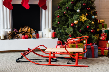 sled and christmas tree with gift boxes near fireplace 免版税图像