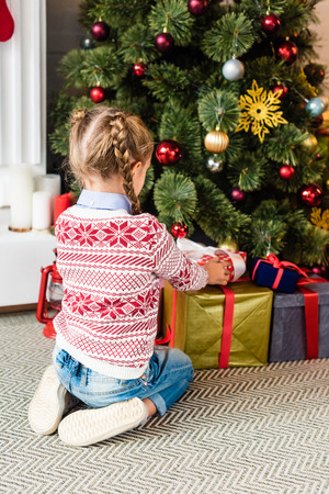 back view of cute kid opening gift boxes under christmas tree