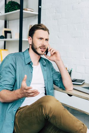 irritated young male freelancer talking on smartphone at table