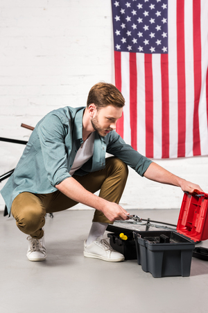 handsome young man putting adjustable wrench in tools box in front of wall with american flag 免版税图像