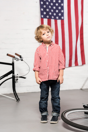 adorable little boy looking at camera near disassembled bicycle at workshop