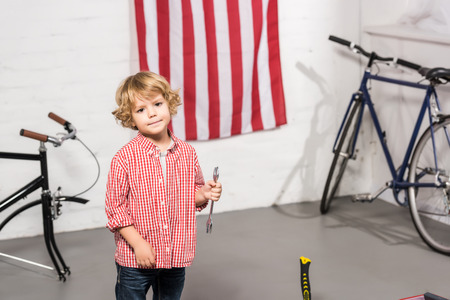 selective focus of little kid standing with spanner near bicycles at workshop