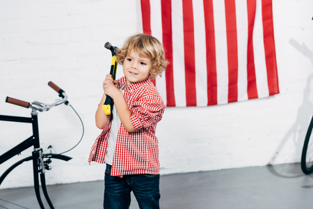 cheerful curly boy holding hammer near disassembled bicycle