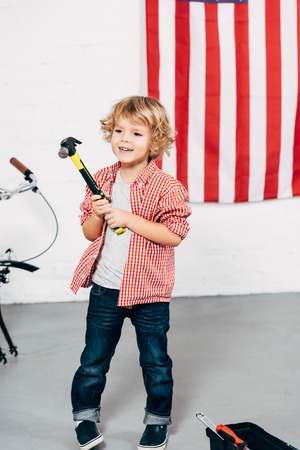 selective focus of happy adorable boy holding hammer