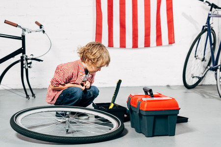 child sitting near tools boxes near disassembled bicycle wheel at workshop Stock Photo