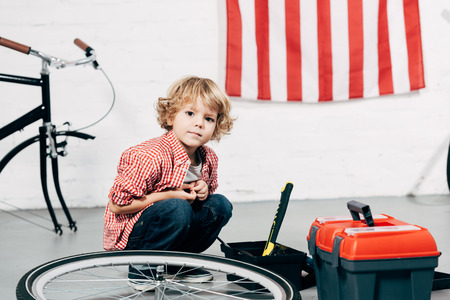 adorable little boy sitting near tools boxes near disassembled bicycle at workshop