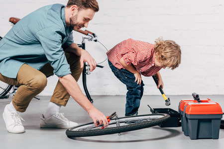side view of male repairman fixing bicycle wheel with pliers while his little son standing near with tools box in workshop Stock Photo
