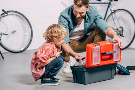 father and adorable little son sitting near opened tools box in bicycle workshop