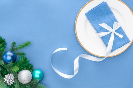flat lay with napkin wrapped by festive ribbon on plate near evergreen tree branches with christmas balls isolated on blue