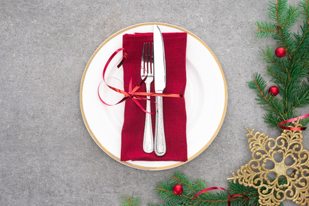 top view of served plate with fork and knife wrapped by red festive ribbon on surface with evergreen branches decorated by christmas balls and golden star
