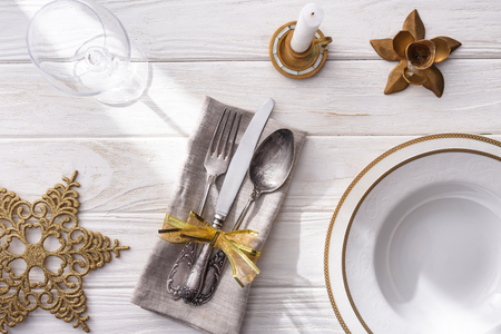 top view of wine glass, plate with golden christmas balls, candle and fork, spoon, knife wrapped by ribbon on wooden table