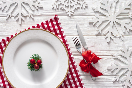 flat lay with evergreen branch, christmas balls on plate near fork and knife wrapped by red festive ribbon surrounded by decorated snowflakes