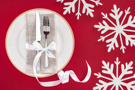 elevated view of plate with fork and knife wrapped by festive ribbon on plate surrounded by snowflakes isolated on red