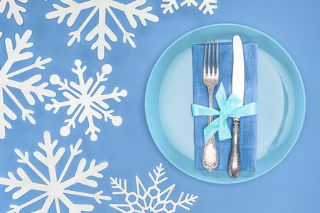 top view of fork and knife wrapped by festive ribbon on plate surrounded by snowflakes isolated on blue Reklamní fotografie