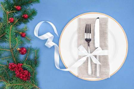 top view of fork and knife wrapped by ribbon on plate near evergreen branches with christmas balls and red berries isolated on blue