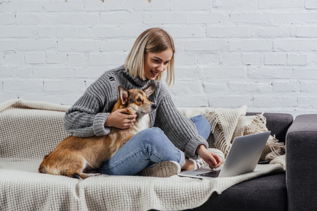 smiling young blonde woman sitting with welsh corgi dog on sofa and using laptop