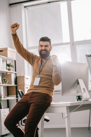happy bearded adult businessman wearing blank security tag and holding arms up in excitement