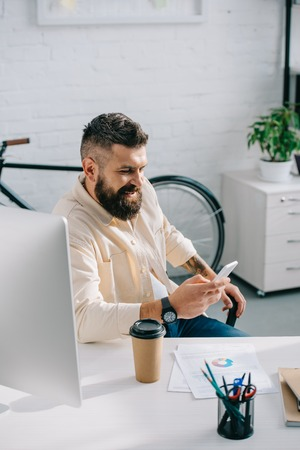 Smiling bearded businessman sitting at desk and looking at smartphone in modern office
