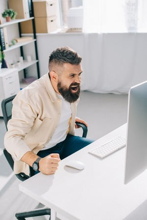 Impulsive businessman sitting in office chair, screaming and beating fist on desk Stock Photo