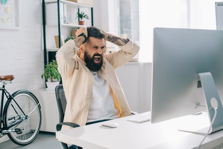 Impulsive bearded businessman with hands on head sitting at computer desk and screaming in office Stock Photo