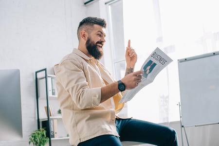 Cheerful businessman reading newspaper in modern office
