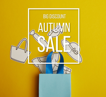 top view of blue shopping bag with paper clothes on yellow background, autumn sale inscription Stock Photo