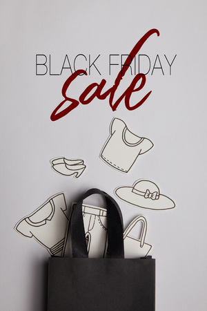 top view of black shopping bag with ssss inscription and paper clothes on grey background, shopping concept Stock Photo