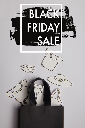 top view of black shopping bag and paper clothes on grey background, black friday sale concept Stock Photo