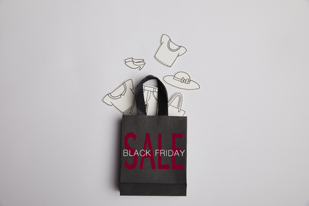top view of black shopping bag with black friday sale inscription and paper clothes on grey background Stock Photo