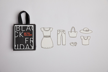 top view of paper bag with black friday sale sign and paper clothes on grey background
