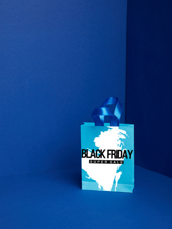 close up view of paper shopping bag on blue backdrop with black friday super sale Stock Photo