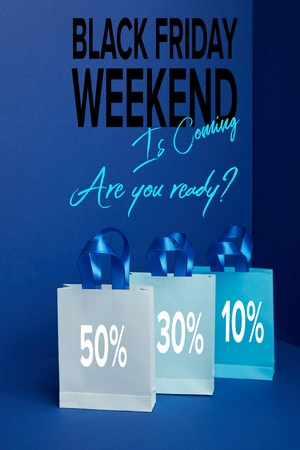 close up view of paper shopping bags arranged on blue with black friday weekend is coming are you ready?