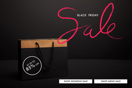 close up view of paper shopping bag on black backdrop with black friday sale Stok Fotoğraf