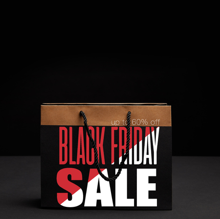 close up view of paper shopping bag on black backdrop with black friday sale and 60 percents discount