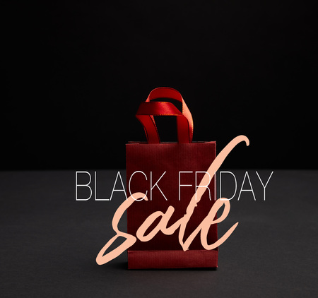 close up view of red paper shopping bag on black backdrop with black friday sale