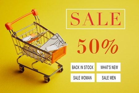close up view of little shopping trolley with paper clothes on yellow backdrop, sale banner concept