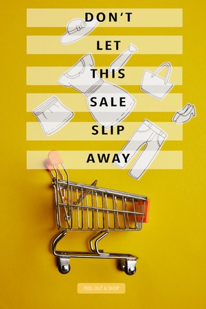 top view of little shopping trolley with paper clothes on yellow backdrop, dont let this sale slip away inscription Фото со стока