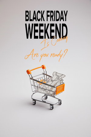 close up view of shopping cart with little goods made of paper on grey background, black friday weekend inscription Stock Photo