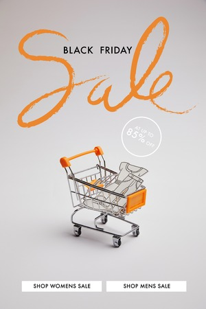 close up view of shopping cart with little goods made of paper on grey background, black friday sale inscription Stock Photo