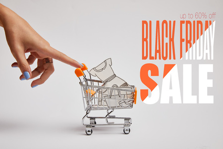 cropped shot of female hand and little shopping cart with paper clothes on grey background, black friday sale inscription